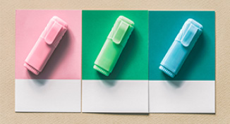 Image of Three different coloured highlighters on three notebooks