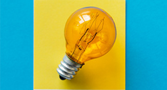 Image of Light bulb against yellow square background